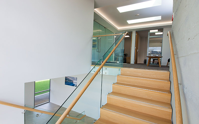 Commercial stairs with central steel stringer and American Oak treads and risers. Raised stainless steel strips create a non-slip nosing.